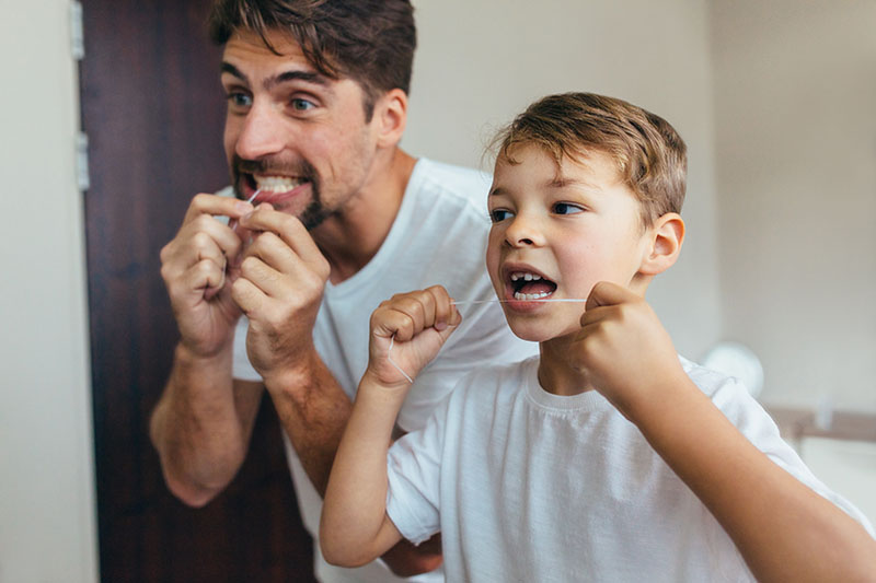 father and son flossing together | Foothill Dental Care